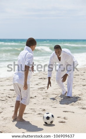 A happy African American man and boy, father and son, playing football soccer on a beach