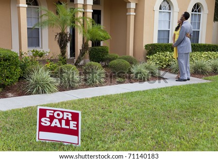 A happy African American man and woman couple house hunting outside a large house with a For Sale sign