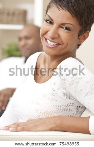A happy African American man and woman couple in their thirties sitting at home, the woman is in focus in the foreground the man out of focus in the background.