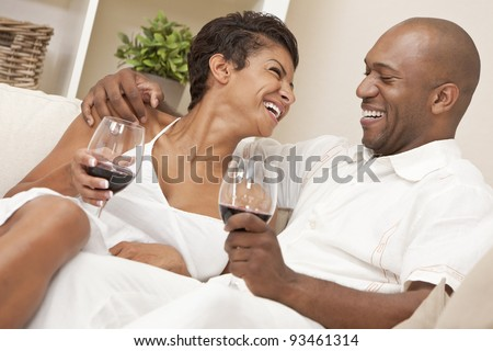 A happy African American man and woman couple in their thirties sitting at home together laughing and drinking glasses of red wine.