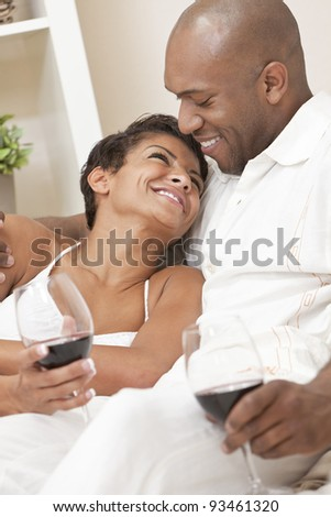 A happy African American man and woman couple in their thirties sitting at home together smiling and drinking glasses of red wine.
