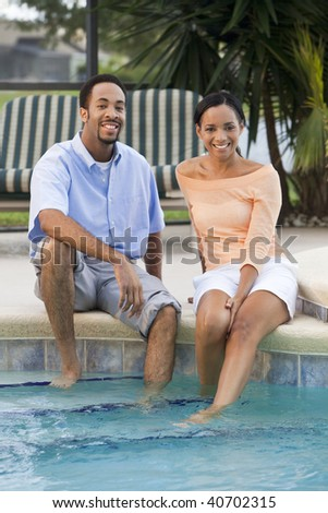 A happy African American man and woman couple in their thirties sitting with their feet in a swimming pool