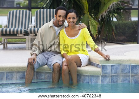 stock photo : A happy African American man and woman couple in their thirties sitting with their feet in a swimming pool.