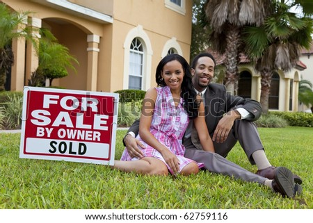 A happy African American man and woman couple outside a large house with a For Sale Sold sign