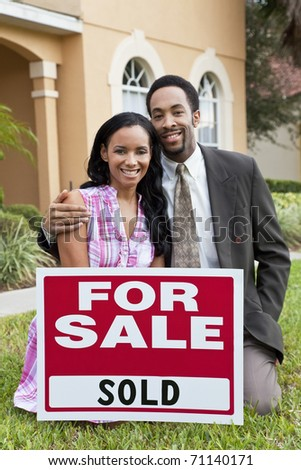 A happy African American man and woman couple outside a large house with a For Sale Sold sign celebrating the purchase of a property