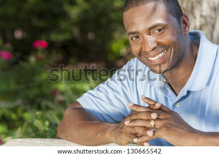 A happy African American man sitting outside and smiling with perfect white teeth
