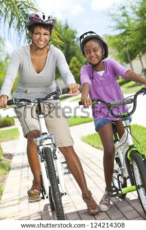 A happy African American woman and child, mother & daughter, cycling together.