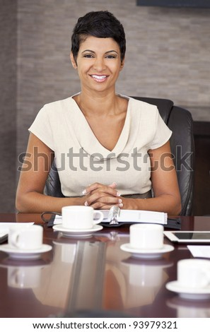 A happy African American woman, businesswoman, sitting & smiling at an office boardroom table