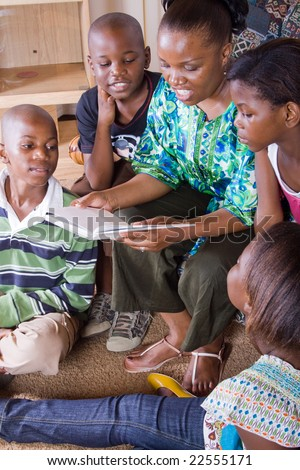 a happy african mother reading a book to her 4 children in living room