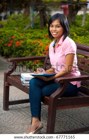 A happy and attractive college student smiles and writes into her notepad.  20s female Asian Thai model of Chinese descent.