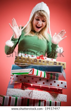 A happy and surprised beautiful caucasian girl receiving christmas gifts