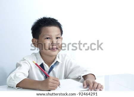 A happy Asian boy holding pencil on white background