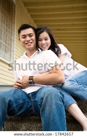 A happy asian couple sitting on the porch in front of their house