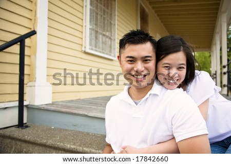 A happy asian couple sitting on the porch in front of their house - stock photo