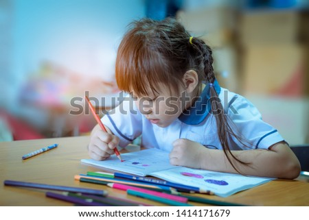 A happy asian girl is painting homework picture with verity crayon color on the table.