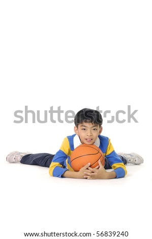 A happy asian little boy relaxing with his basketball