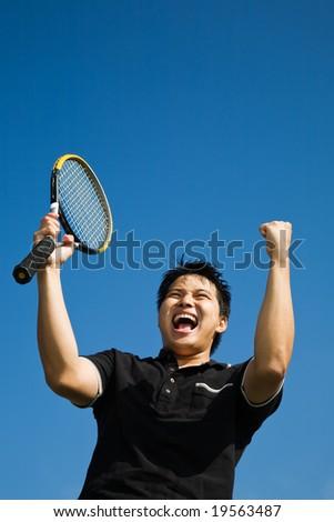 A happy asian tennis player in joy of winning