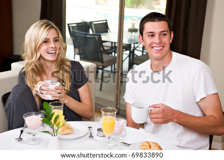 A happy, attractive couple eats breakfast together