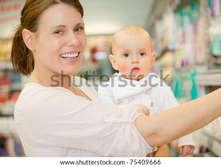 A happy baby and mother in a grocery store buying groceries