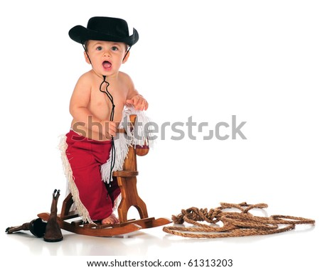 A happy baby boy shouting as he rides his rocking horse.  Isolated on white.