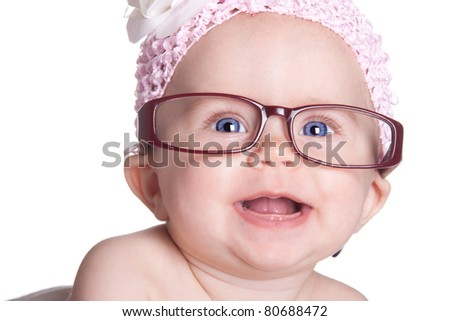 A happy baby girl smiles with her glasses on.  She has a beautiful white bow on.