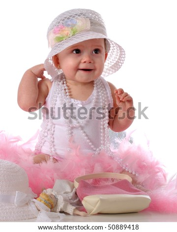 A happy baby girl wearing beads, a fancy hat, and feathery, pink boas over her girlie undershirt.