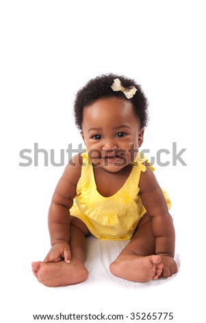 a happy baby smiling as she sits on white fabric - isolated except for the area she is sitting in