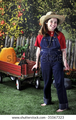 A happy, barefoot girl pulling a wagon with pumpkins and a rooster past an apple orchard.