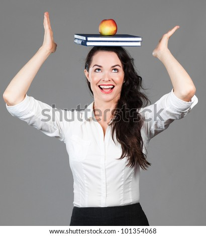 A happy beautiful business woman balancing books and an apple on her head