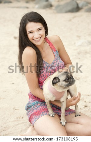A happy beautiful female model posing at the beach with a cute pug.