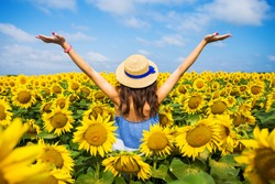A happy, beautiful young girl in a straw hat is standing in a large field of sunflowers. Summer time. Back view.