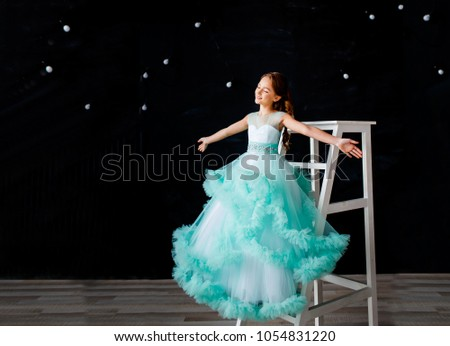 Stock Photo a happy beautiful young girl with hands stretched in a lush turquoise dress on the ladder on black background. concept of happiness and freedom