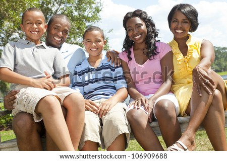 A happy black African American family of two parents and three children, two boys one girl, sitting together outside.
