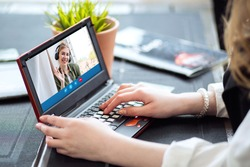 A happy blonde woman using a laptop computer to video call friends and parents, a girl sitting at home on the window