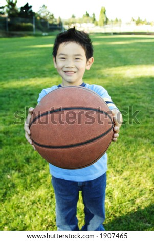 A happy boy handing a basketball (shallow DOF, focus on the ball)