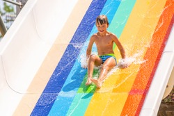 A happy boy on water slide in a swimming pool having fun during summer vacation in a beautiful aqua park. A boy slithering down the water slide and making splashes.