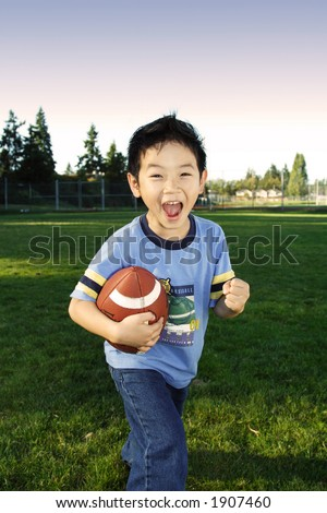 A happy boy playing football outdoor