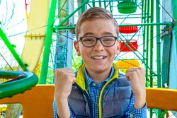 A happy boy with glasses  is riding a Ferris wheel