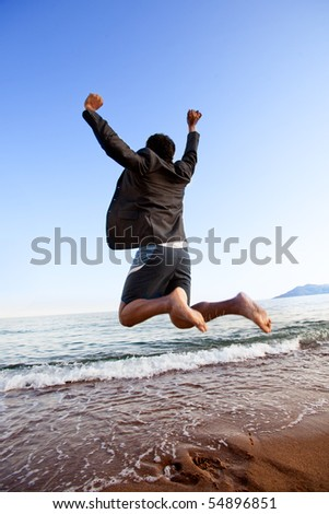A happy business man jumping by the ocean - happy successful concept - stock photo