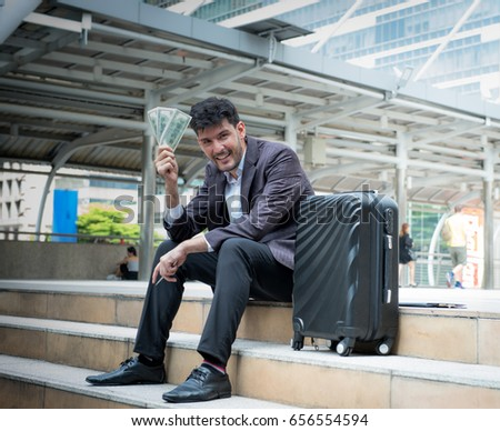 A happy businessman holds a handful of green American money sitting on stairs with suitcase in city, Businessman holding dollars and smiling at the camera, Age 20-30 year, #656554594