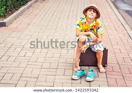 A happy but tired traveling boy sits on a suitcase barefoot in the middle of a city street. Sneakers are next to bare feet. Concept pleasant travel fatigue, tourism