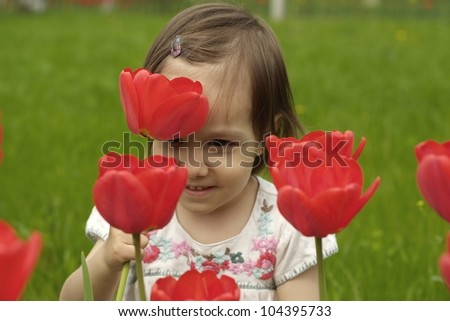 A happy Caucasian baby in flowers on the street