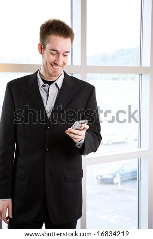 A happy caucasian businessman receiving a text message - stock photo