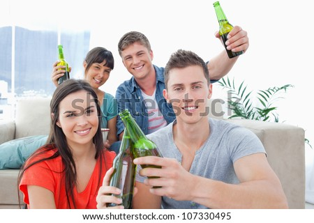 A happy celebrating group of friends raising and clinking bottles in happiness