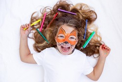 a happy cheerful child with a painted face lies with colored markers