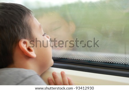 A happy child boy is sitting by the window on a train, looking outside and smiling