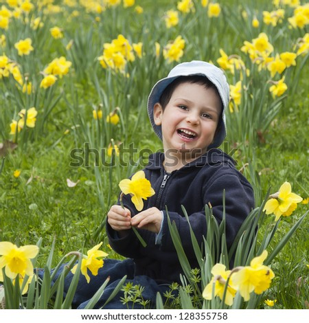A happy child boy sitting amongst daffodil flowers in a spring  garden or in a park.