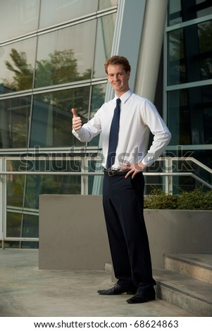A happy corporate employee smiling and giving the thumbs up outside of a modern office park.  20s handsome caucasian male British model.