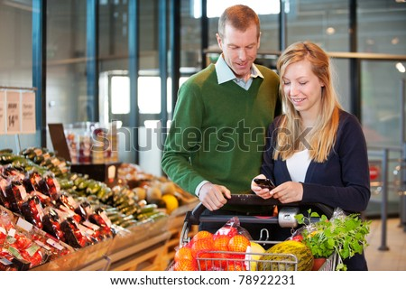 A happy couple buying groceries looking at grocery list on phone