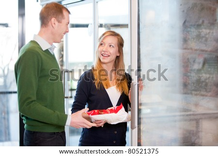 A happy couple choosing groceries from the frozen food section in a supermarket
